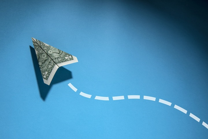 Dollar bill folded into a paper airplane charting a course over lending options, such as asset based lending